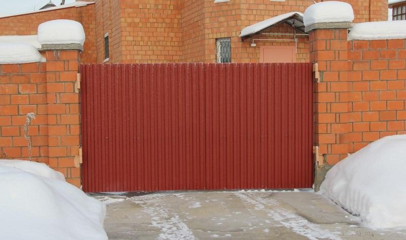 Распашные ворота из профнастила в заборе из кирпича