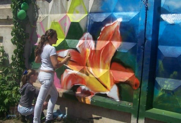 Дети рисуют полноценные рисунке на бетонном заборе