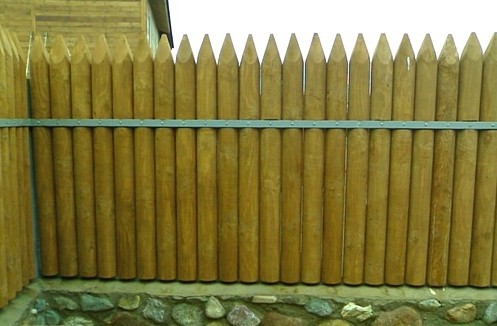 Забор в виде частокола из бревен