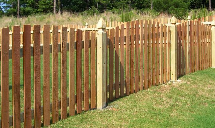 Деревянный забор из штакетника, ко который установлен волною